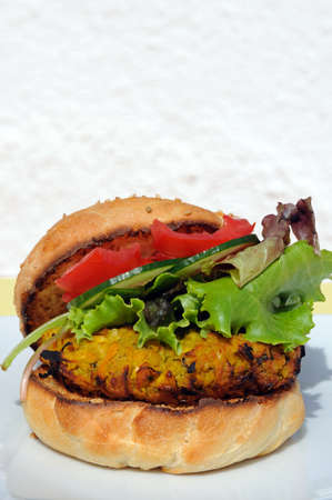 sesame seed bun: Vegetarian chickpea, sweetcorn and carrot burger with salad in a sesame seed bun