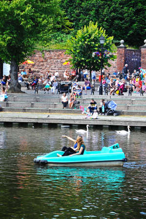 Chester, United Kingdom - July 22, 2014 - People enjoying sitting on the River Dee embankment with a pedalo in the foreground, Chester, Cheshire, England, UK, Western Europe.