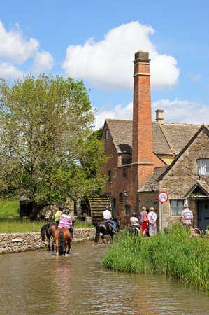 molino de agua: Baja Masacre, Reino Unido - 12 de junio 2014 - Grupo de personas montando caballos a lo largo del r�o de ojos con el antiguo molino de agua en la parte trasera, Baja Masacre, Cotswolds, Gloucestershire, Inglaterra, Reino Unido, Europa occidental. Editorial