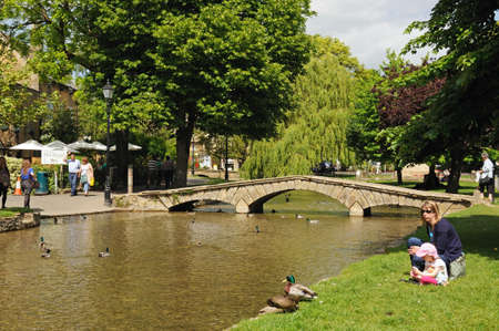 cotswold: Bourton-on-the-Water, UK - June 12, 2014 - Stone footbridge across the River Windrush with tea-rooms to the rear, Bourton on the Water, Gloucestershire, England, UK, Western Europe.