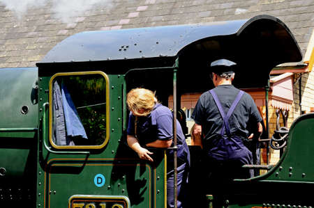 footplate: Arley, UK - July 10, 2014 -Steam Locomotive 7800 Class 4-6-0 Erlestoke Manor number 7812 in Great Western Railways green at the railway station with train workers on the footplate, Severn Valley Railway, Arley, Worcestershire, England, UK, Western Europe.