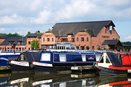 moorings: Barton Marina, - May 21, 2014 - Narrowboats on their moorings in the canal basin with shops, bars and restaurants to the rear, Barton Marina, Barton-under-Needwood, Staffordshire, England, UK, Western Europe. Editorial