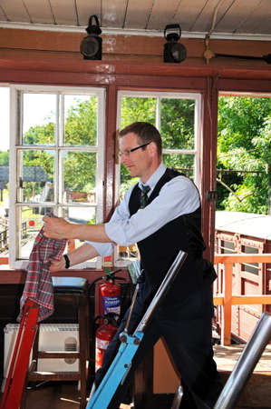 Highley, UK - July 10, 2014 - Signalman operating the Main Line lever on the mechanical lever frame inside the signal box at the railway station, Highley, Worcestershire, England, UK, Western Europe. Editorial