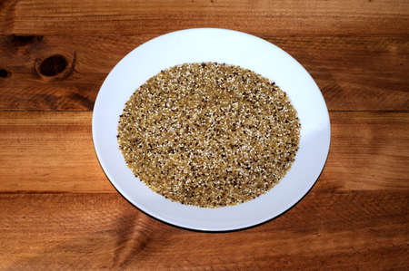 insoluble: Dried red and white Quinoa seeds mixed with Bulgar wheat on a white plate.