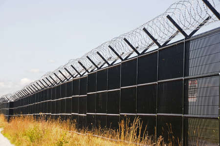 bluesky: Coiled barbed wire on top of a security fence Stock Photo