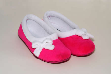 white trim: A pair of Ladies pink slippers with white trim.