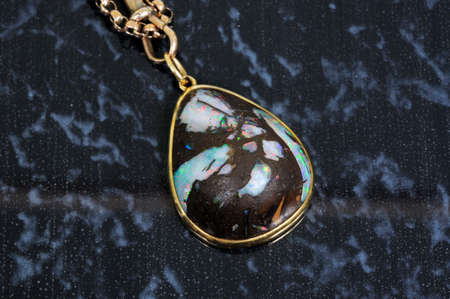 opalescent: Wood opal pendant against a dark grey background.