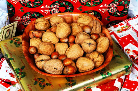 A wooden bowl full of hazelnuts and walnuts sitting on a pile of Christmas presents, England, UK, Western Europe. Stock Photo