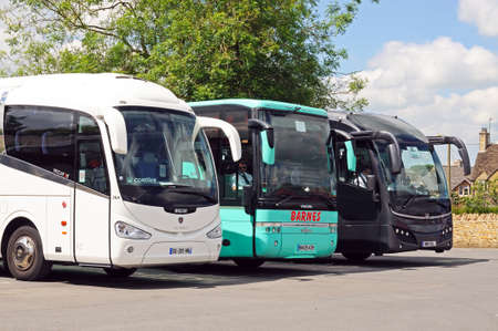 Three tourist coaches parked in a row in a coach and car park, Bourton on the Water, Gloucestershire, England, UK, Western Europe.