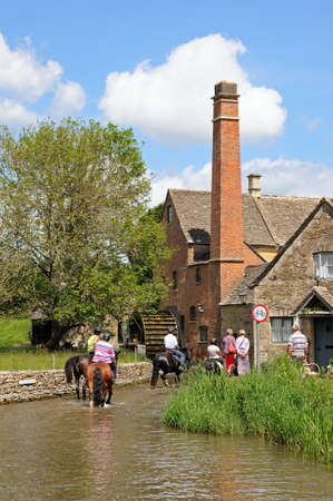 watermill: Group of people riding horses along the River Eye with the old watermill to the rear, Lower Slaughter, Cotswolds, Gloucestershire, England, UK, Western Europe.