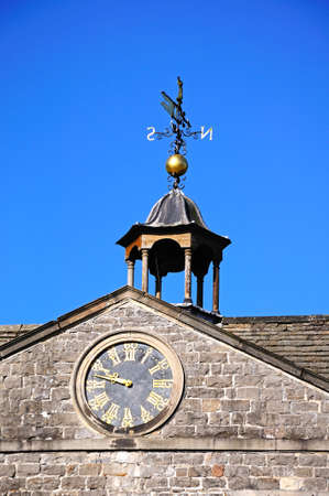 top 7: Tissington, Reino Unido - 07 de septiembre 2014 - Reloj y veleta detalle en la parte superior de Tissington Hall, Tissington, Derbyshire, Inglaterra, Reino Unido, Europa occidental. Editorial