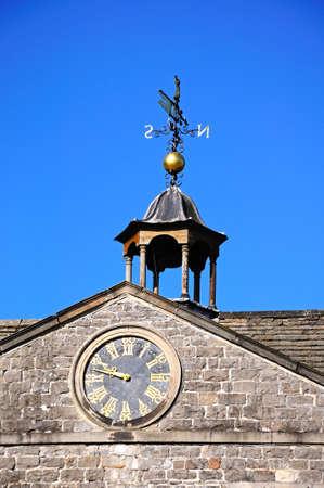 jacobean: Tissington, UK - September 7, 2014 - Clock and weathervane detail on top of Tissington Hall, Tissington, Derbyshire, England, UK, Western Europe.