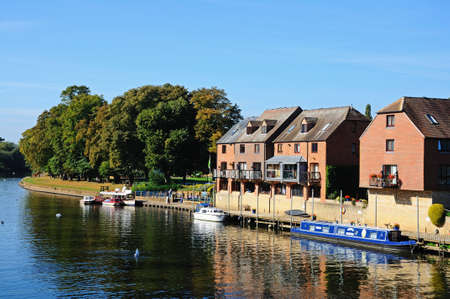 worcestershire: Evesham, UK - September 8, 2014 - Narrowboat moored along the River Avon with apartments to the rear, Evesham, Worcestershire, England, UK, Western Europe.