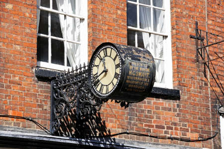 dated: Clock in a wrought iron frame dated 1883 on the front of a shop building along the High Street, Tewkesbury, Gloucestershire, England, UK, Western Europe.