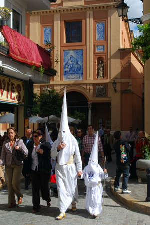 holy week in seville: Members of the Candelaria brotherhood walking along the street during Santa Semama, Seville, Seville Province, Andalusia, Spain, Western Europe.