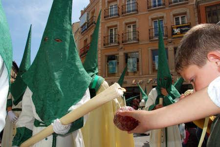 semana: Malaga, Spain - April 5, 2009 - Members of the Pollinca brotherhoo walking through the city centre dripping candle wax onto wax balls during Santa Semana, Malaga, Malaga Province, Andalusia, Spain, Western Europe.