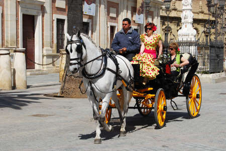 horse drawn carriage: Seville, Spain - April 12, 2008 - Spanish women in traditional dress travelling in a horse drawn carriage by the Cathedral, Seville, Seville Province, Andalusia, Spain, Western Europe. Editorial