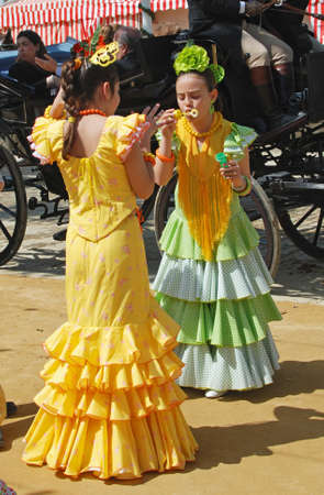 blowing bubbles: Seville, Spain - April 12, 2008 - Spanish girls in traditional dress blowing bubbles at the Seville Fair, Seville, Seville Province, Andalusia, Spain, Western Europe.