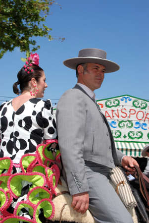 Seville, Spain - Arpil 12, 2008 - Spanish couple in traditional dress sitting on a horse with Casitas to the rear at the Seville Fair, Seville, Seville Province, Andalusia, Spain, Western Europe. Редакционное