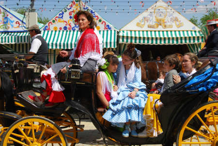 horse drawn carriage: Seville, Spain - April 12, 2008 - Spanish family in traditional dress travelling in a horse drawn carriage at the Seville Fair, Seville, Seville Province, Andalusia, Spain, Western Europe.