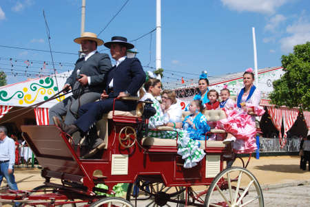 horse drawn carriage: Spanish family in traditional dress travelling in a horse drawn carriage at the Seville Fair, Seville, Seville Province, Andalusia, Spain, Western Europe.