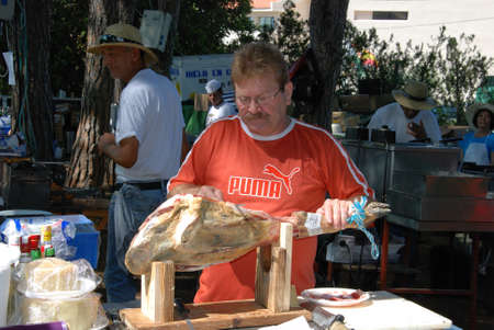 cured ham: Man carving pieces of cured ham (Jamon Serrano) from the joint during the Romeria San Bernabe procession, Marbella, Costa del Sol, Malaga Province, Andalusia, Spain, Western Europe.