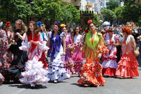 flamenca bailarina: Mujer caminando por la calle vistiendo trajes de flamenca durante la Romer�a de San Bernab�, Marbella, Costa del Sol, provincia de M�laga, Andaluc�a, Espa�a, Europa Occidental.