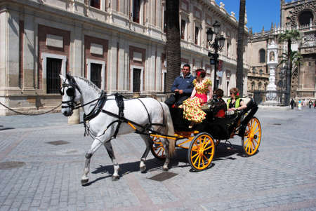 horse drawn carriage: Spanish women in traditional dress travelling in a horse drawn carriage outside the Cathedral, Seville, Seville Province, Andalusia, Spain, Western Europe.
