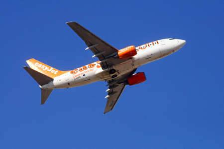 boeing: Easyjet Boeing 737-700 taking off against a blue sky.