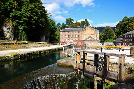 derbyshire: Cromford Mill (water powered cotton spinning mill) with a sluice mechanism in the foreground, Cromford, Derbyshire, England, UK, Western Europe. Editorial