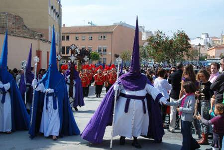 semana: Members of the Huerto brotherhood walking through the city centre streets during Santa Semana, Malaga, Malaga Province, Andalusia, Spain, Western Europe.