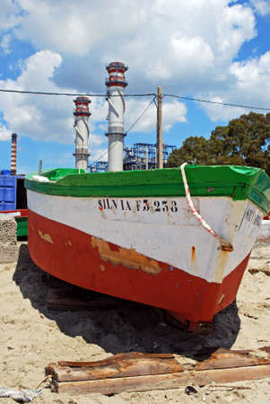 petrochemical: Traditional wooden red and white fishing boat with petrochemical oil refinery to the rear, Puente Mayorga, Cadiz Province, Andalusia, Spain, Western Europe. Editorial