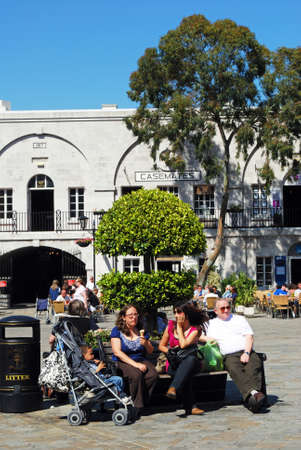 grand child: Tourists sitting on a bench in Grand Casemates Square, Gibraltar, United Kingdom, Western Europe.