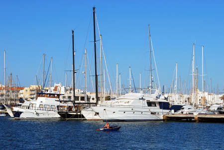 rowing boat: Man in a rowing boat in the marina with yachts and apartments to the rear, Almerimar; Almeria Province, Andalusia, Spain, Western Europe.