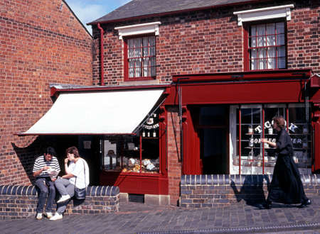country living: Couple sitting eating on a wall outside a Victorian shop with a Victorian woman walking along in the Black Country Living Museum, Dudley, West Midlands, England, UK, Western Europe.