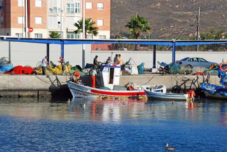 dockside: Fishermen sorting their fishing nets on the dockside, Puerto de la Atunara, Costa del Sol, Cadiz Province, Andalusia, Spain, Western Europe.