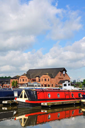 moorings: Narrowboats on their moorings in the canal basin with shops, bars and restaurants to the rear, Barton Marina, Barton-under-Needwood, Staffordshire, England, UK, Western Europe. Editorial