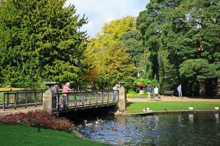 derbyshire: Tourists standing on the footbridge in the Pavilion Gardens, Buxton, Derbyshire, England, UK, Western Europe.