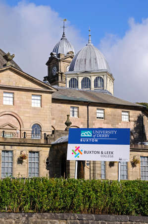 derbyshire: The Devonshire Royal Hospital, also known as the Devonshire Dome with a University of Derby sign in the foreground, Buxton, Derbyshire, England, UK, Western Europe.