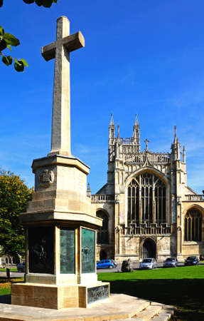 indivisible: Cathedral church of St Peter and the Holy and Indivisible Trinity with a war memorial cross in the foreground, Gloucester, Gloucestershire, England, UK, Western Europe.