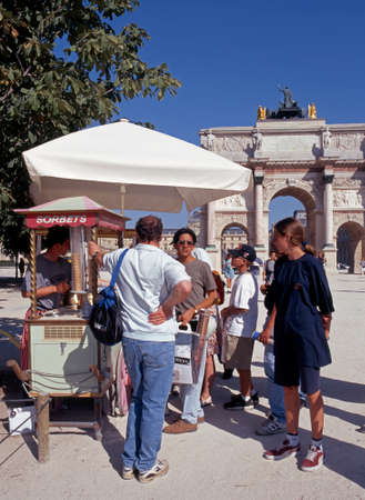 carrousel: Tourists standing by an ice cream stall with the Arc de Triomphe du Carrousel to the rear, Paris, France, Western Europe.