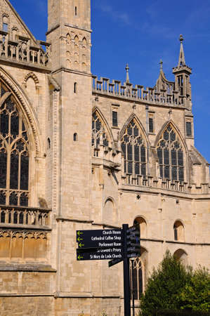 indivisible: Cathedral church of St Peter and the Holy and Indivisible Trinity with a signpost in the foreground, Gloucester, Gloucestershire, England, UK, Western Europe. Stock Photo