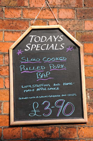 pulled: Todays Special chalkboard against a brick wall advertising Pulled Pork Bap