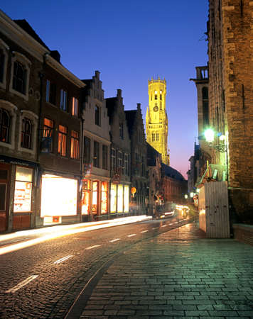 evenings: View along Wollestraat with the Belfry lit up at night to the rear Bruges Belgium Western Europe.