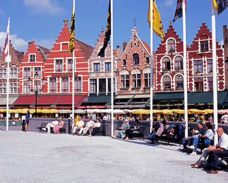 flagpoles: Row of Cafes in the Market Place with flagpoles in foreground and tourists sitting on benches Bruges Belgium Western Europe. Editorial