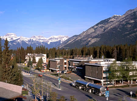 Elevated viwe along the main street through Banff town with snow capped mountains to the rear Banff Banff National Park Alberta Canada.