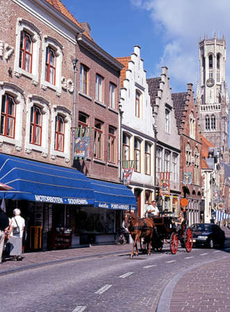 horse drawn carriage: Horse drawn carriage along Wollestraat with the Belfry to the rear Bruges Belgium Western Europe.