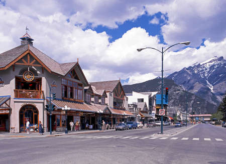 snow capped mountains: View of the shops along the main street through Banff town with snow capped mountains to the rear Banff Banff National Park Alberta Canada. Editorial