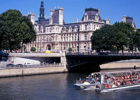 pleasure boat: Hotel De Ville Town Hall with a pleasure boat full of tourists on River Seine in the foreground Paris France Western Europe.