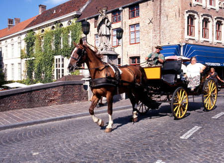 horse drawn carriage: Tourists travelling in a horse drawn carriage crossing the Dijver at Wollestraat Bruges Belgium Western Europe. Editorial